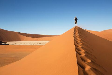 Desert sand dune with a man walking on it