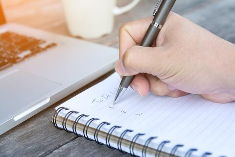 top ten tips for top ten lists - someone writing a list in a notebook