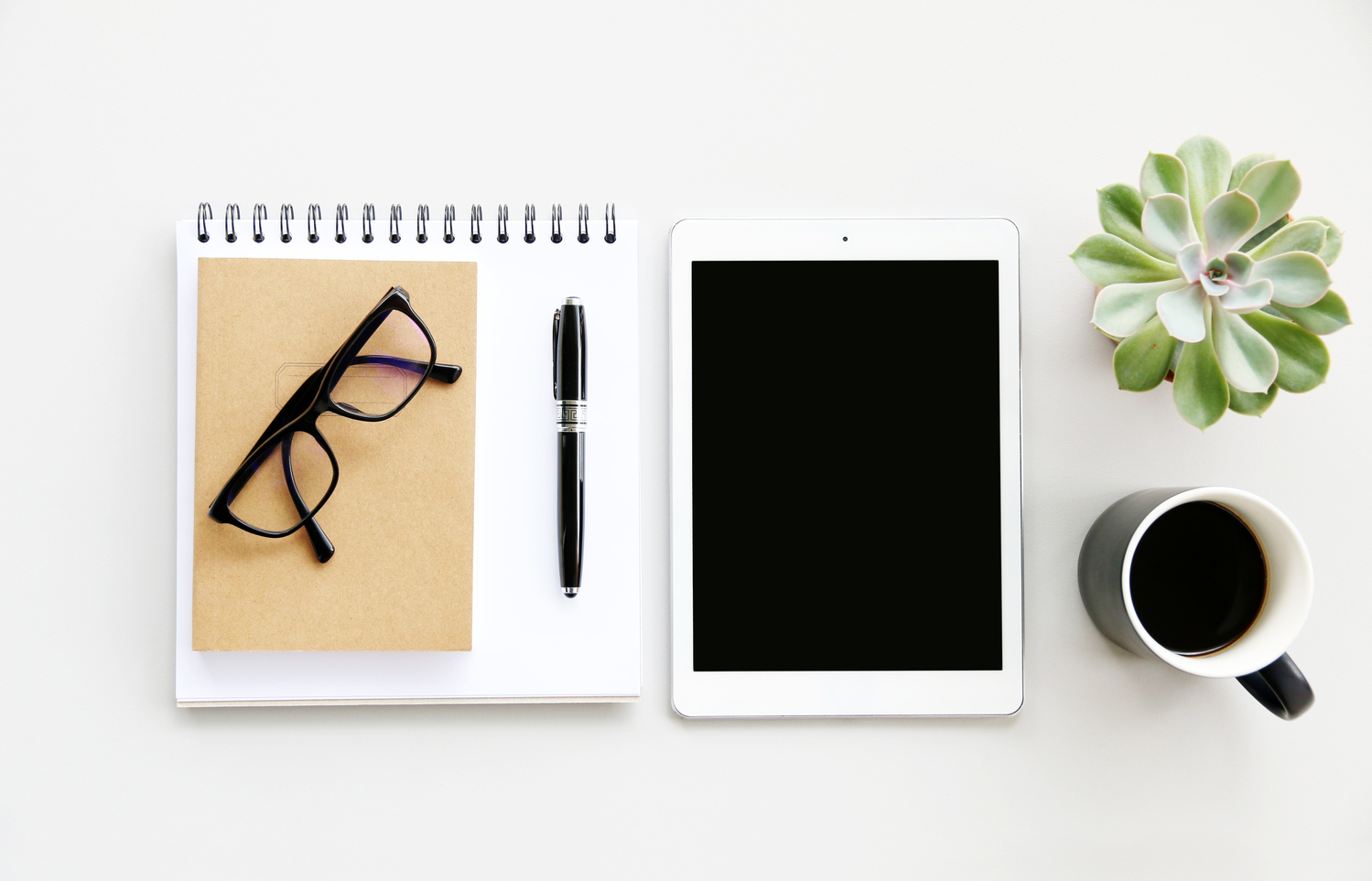Ipad and notepad on desk with plant