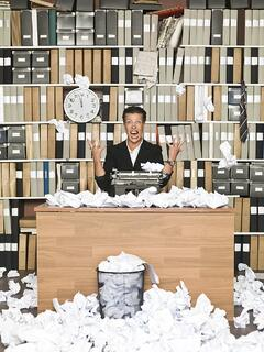 Copywriter surrounded by rejected drafts on paper
