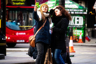 Marketing to Millennials: two girls taking a selfie in the street
