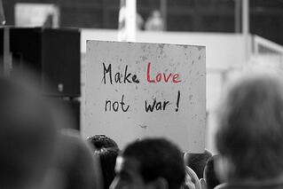 Learn from your competitors: make love not war sign in crowd