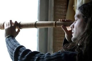 Man looking forward through a telescope