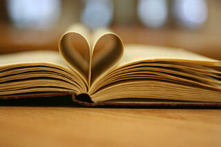 Write with anecdotes and make your message more powerful. Learn to love stories, and learn to write better. Picture shows the pages of a book folded into the shape of a cartoon heart.