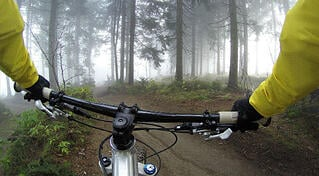 Write with anecdotes: write with impact. Picture is taken from a cyclists point of view, showing the handlebars of a mountain bike.