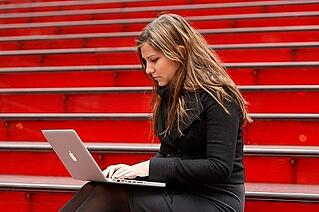 Girl on bleachers with Macbook