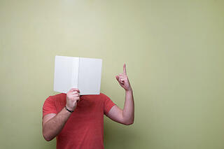 Write with anecdotes: how to make your writing as large as life. Picture shows man holding book up to face and gesturing with his left hand to indicate that he is speaking.