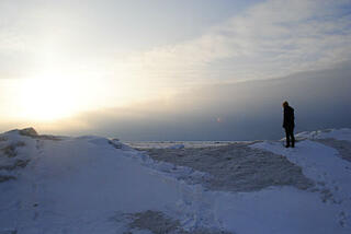 Write with anecdotes: write bigger. Picture shows someone standing on top of a snow drift looking into the sunset.