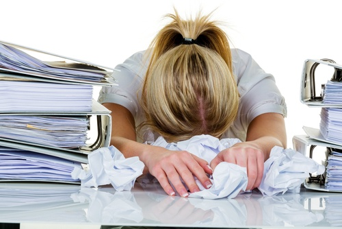 Too much to do: Woman with her head on the desk and too much paperwork