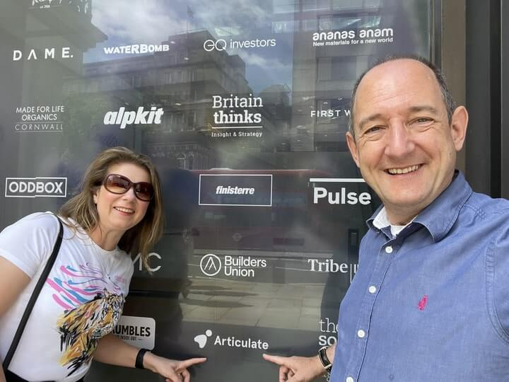 Image of our CEO and CFO outside B Corp certified, Coutts Bank, pointing to the Articulate logo