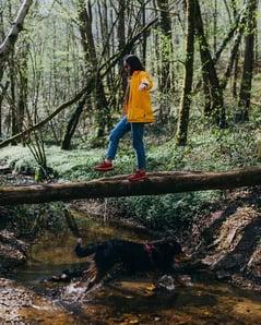 Woman walking across a bridge in a forest