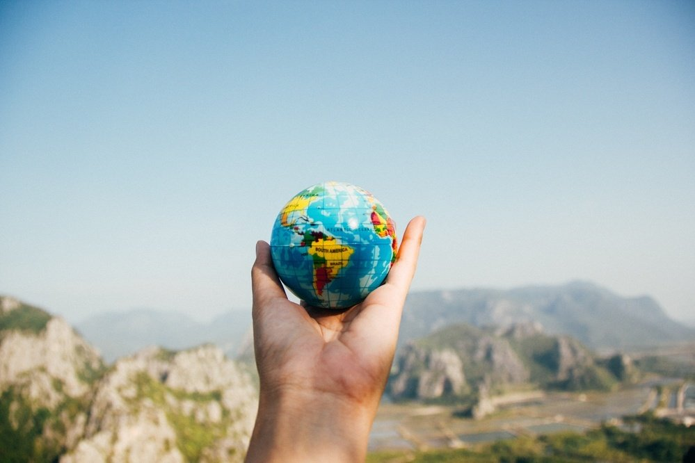 Hand holding up a small globe against a blue sky