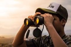 man outside looking through binoculars