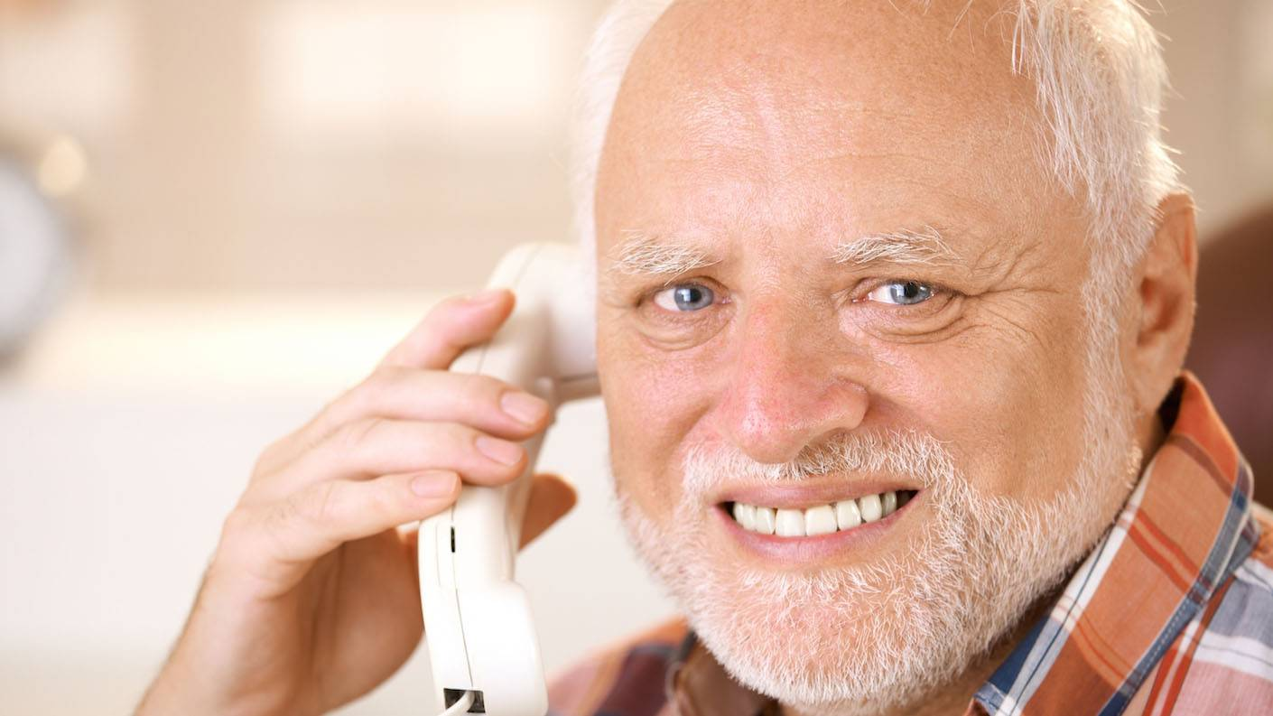 old man on the phone grimacing