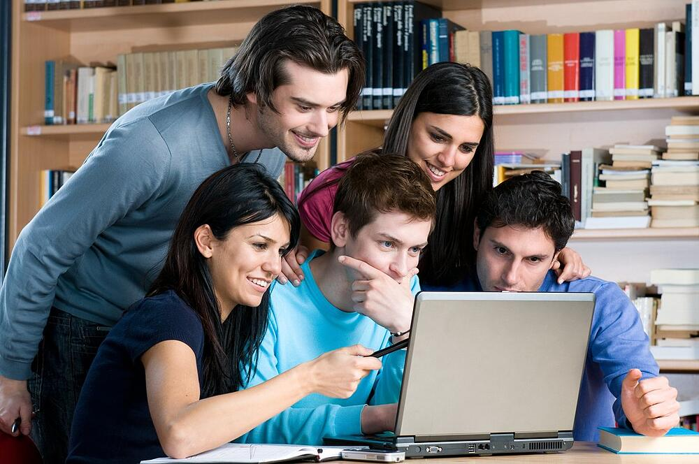 Who do we 'copywrite' for? A group of young people gather round a laptop screen.